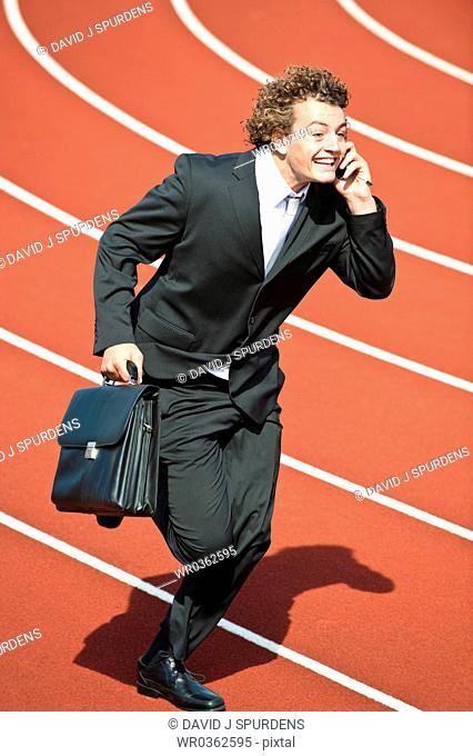 Happy businessman on cell phone sprinting fast on track with briefcase
