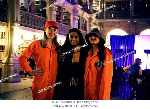 Three college students are posing for a picture, the two girls on the end are wearing orange jumpsuits and hats in order to portray characters from the story...