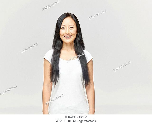 Portrait of smiling woman with long black hair wearing white shirt