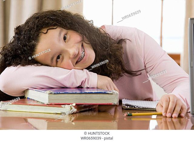 Portrait of a girl leaning on books and smiling