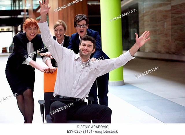 business people group at modern office indoors have fun and push office chair on corridor