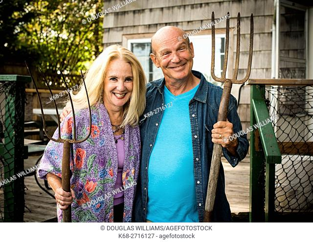 USA, Washington state, Point Roberts, Portrait of smiling senior couple standing in front of house and holding garden forks