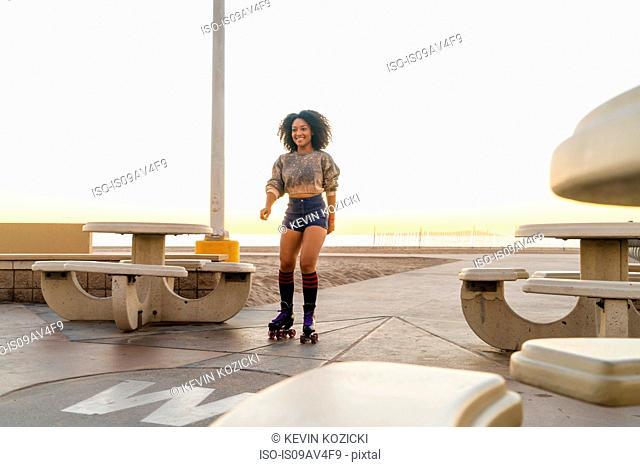 Mid adult woman on rollerskates, near beach