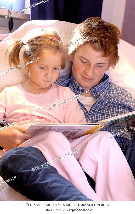 Brother is reading a bedtime story to his sister