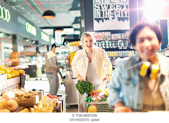 Playful young woman laughing, pushing shopping cart in grocery store market