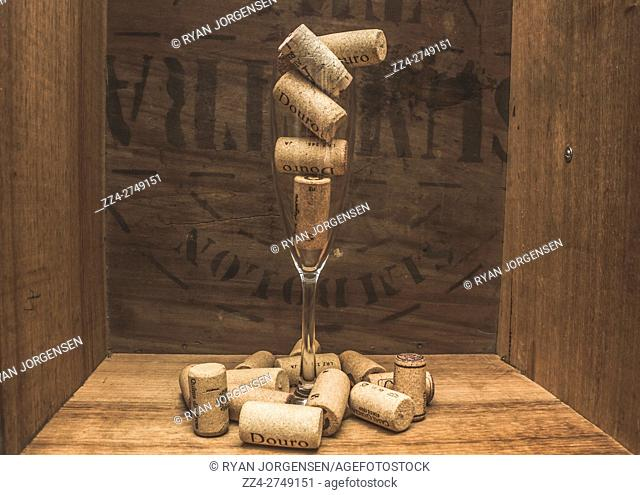 Concept of wine corks in glass and scattered on wood surface. Inside of wooden box