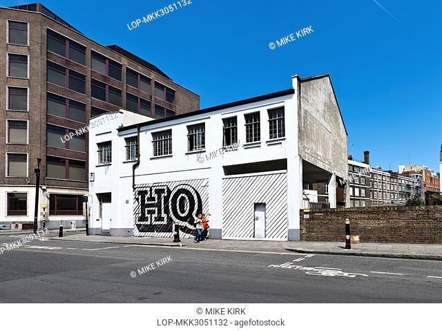 England, London, City of London. Two women walking past a building on Lindsey Street, Smithfield with HQ painted on shutters by Ben Eine