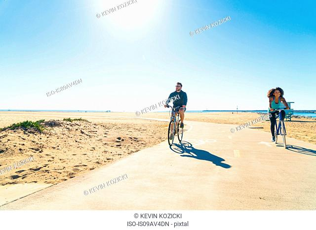 Couple cycling along pathway at beach