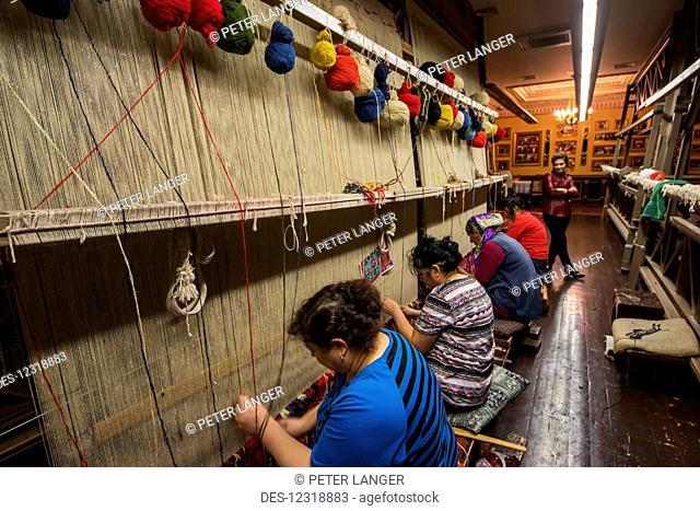Women working on a loom at the weaving workshop of the Azer-Ilme Carpet Weaving Center; Baku, Azerbaijan