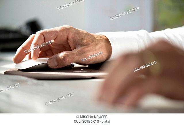Cropped view of man using computer mouse