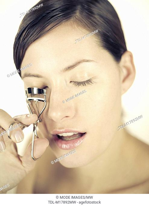 A young woman using eyelash curlers