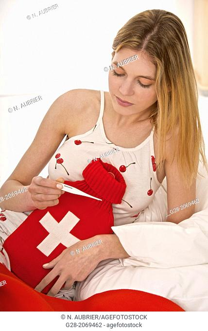 Young beautiful woman in bed, holding a red and white hot water bottle, and a medical thermometer
