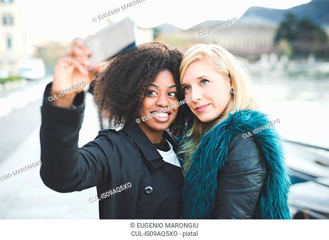 Two young women posing for smartphone selfie at Lake Como, Como, Italy