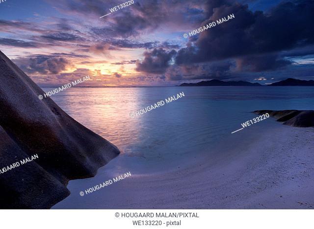 Landscape photo of a colourful sunset on the famous Anse source d'Argent beach. La Digue Island, Seychelles
