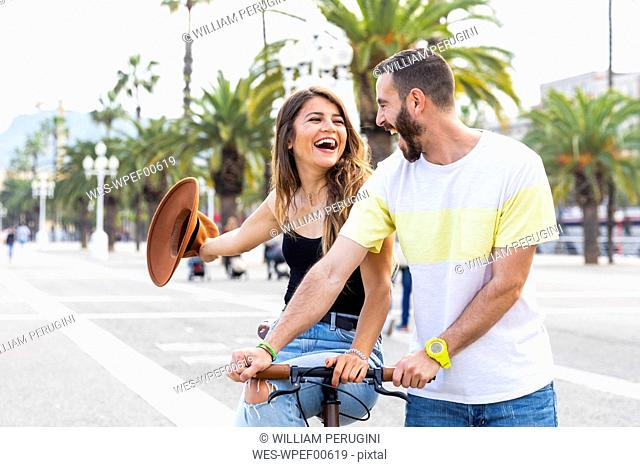 Spain, Barcelona, couple having fun and sharing a ride on a bike together on seaside promenade