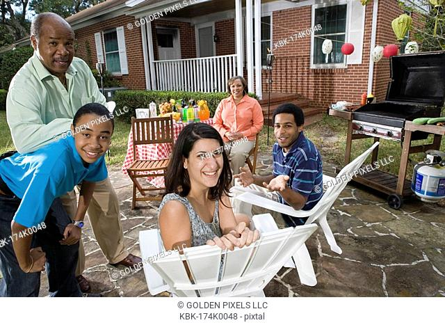 Family and friends enjoying backyard barbeque