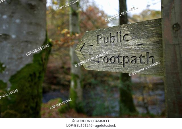 England, Cumbria, Lake District. A wooden sign pointing the way of a public footpath in woodland in the Lake District