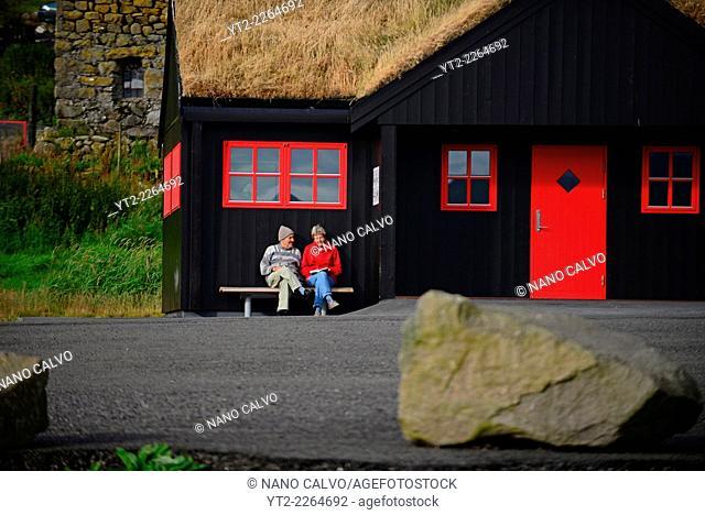 Elderly couple sitting on bench in Kirkjubøur, Faroe Islands