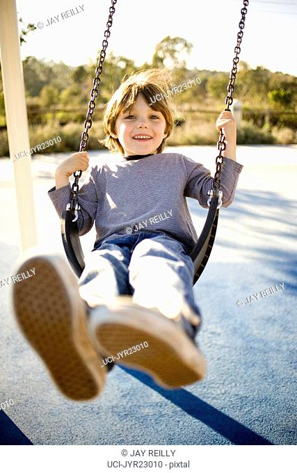 Young boy swinging at playground