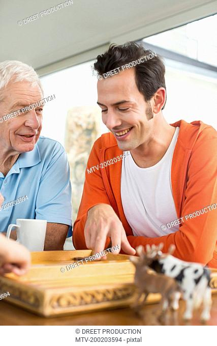 Father and adult son playing backgammon