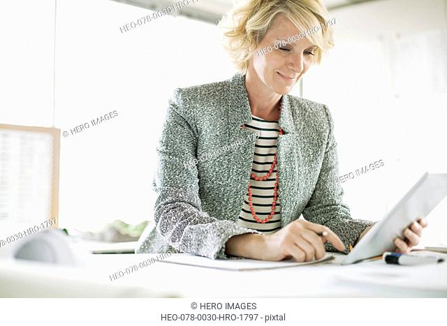 middle-aged businesswoman using pc tablet in modern office