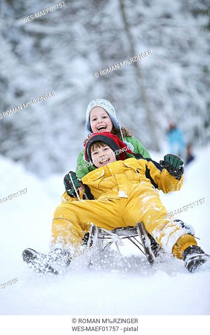Germany, Bavaria, Siblings 8-9 sledding downhill, laughing