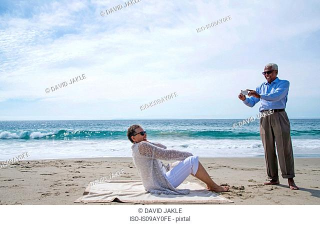 Senior couple on beach, man taking photograph of woman using smartphone