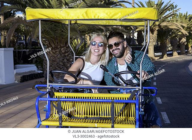 Smiling young man and woman riding on touristic cart and embracing. Lanzarote, Canary Islands, Spain