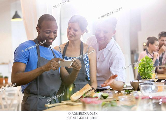 Man photographing food in cooking class kitchen
