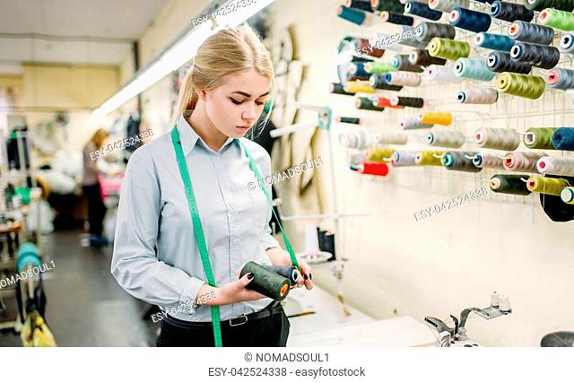 Clothes designer with color threads in hands, manufacture on sewing factory. Female seamstress on dress fabric, dressmaking or tailoring