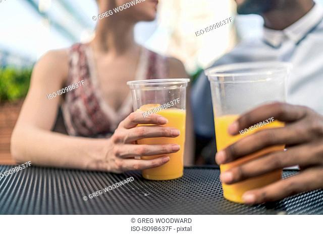 Young couple sitting outdoors, holding plastic drinking glasses, mid section