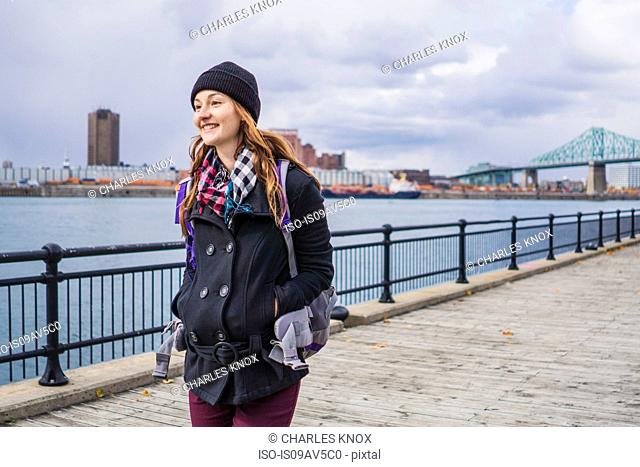 Young woman walking by river, Ile Ste-Helene, Montreal, Quebec, Canada