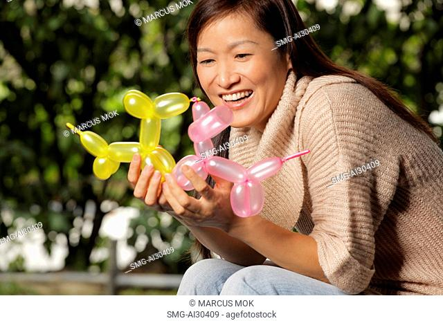 A woman holds two balloon animals and smiles