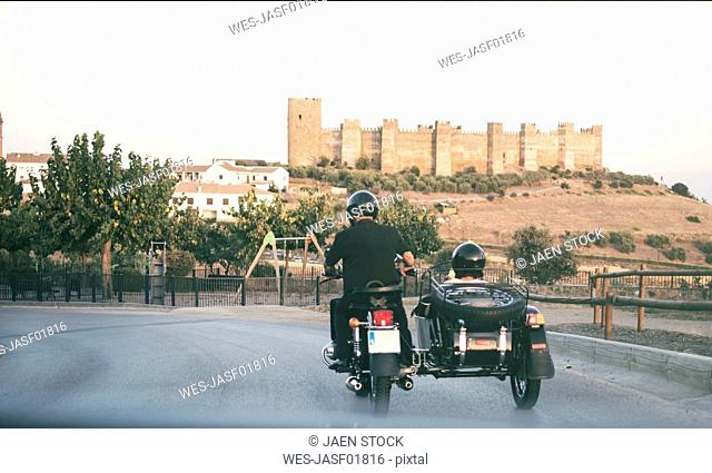 Spain, Jaen, mature couple riding on motorcycle with a sidecar with Banos de la Encina castle in background