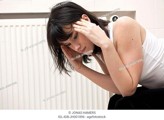 This picture shows a young caucasian woman with brown hair as she sits near her toilet feeling sick / ill in her bathroom