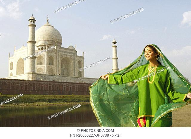 Young woman standing with her eyes closed on the riverbank, Taj Mahal, Agra, Uttar Pradesh, India