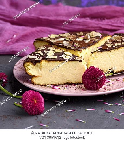 pieces of cheesecake with chocolate on a pink plate, close up