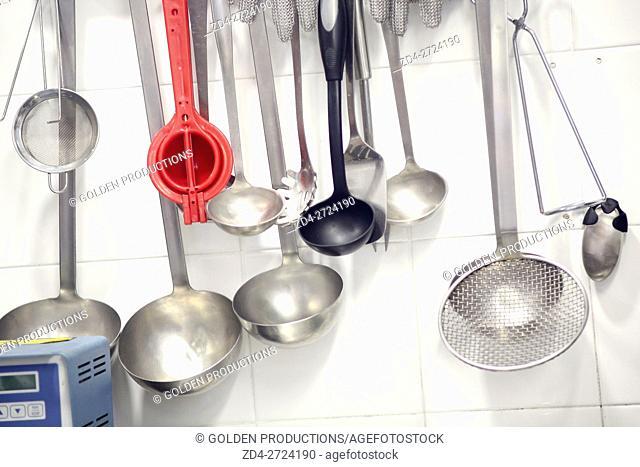 Kitchen utensils hanging by white wall in restaurant kitchen