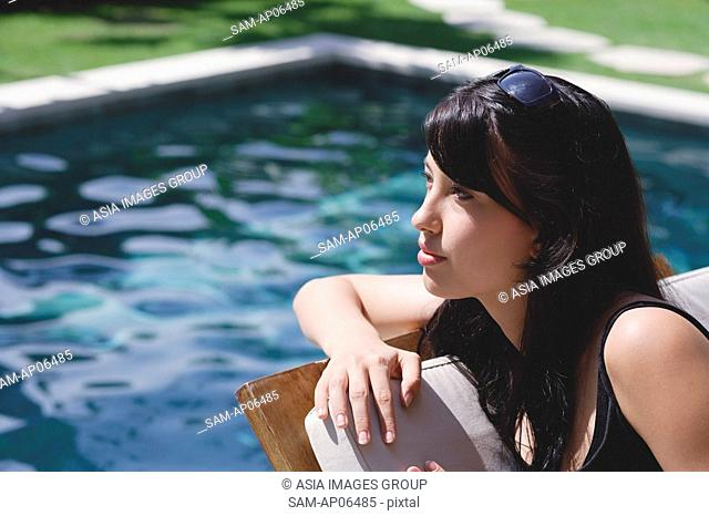 Young woman leaning on deck chair by swimming pool