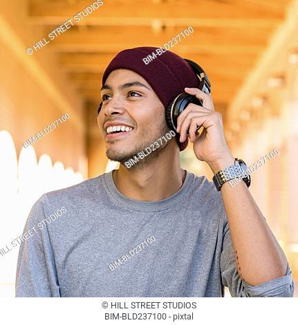 Hispanic man listening to headphones