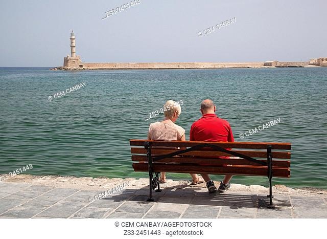 Couple sitting on a bench with the lighthouse in the background at the Venetian harbor of Chania, Crete, Greek Islands, Greece