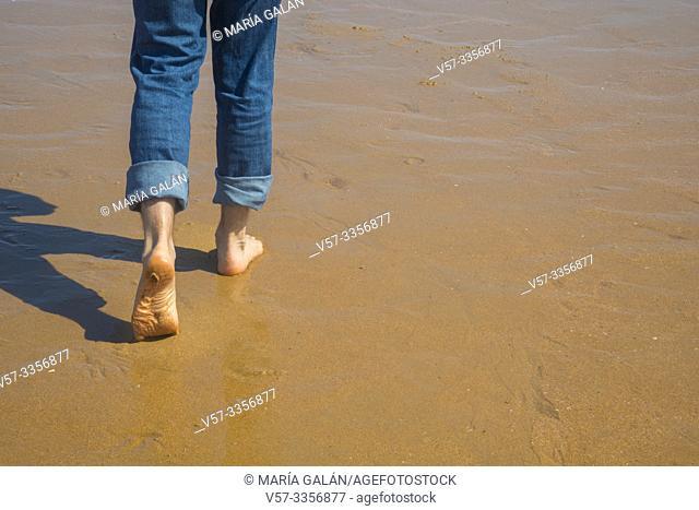 Man' s legs walking along wet sand