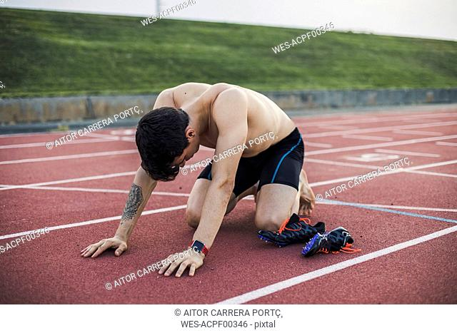 Athlete kneeling on a tartan track after finishing a race