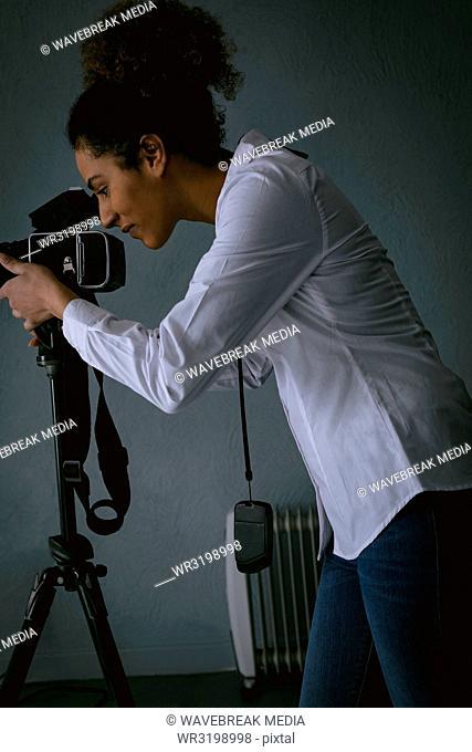 Female photographer clicking photos with digital camera