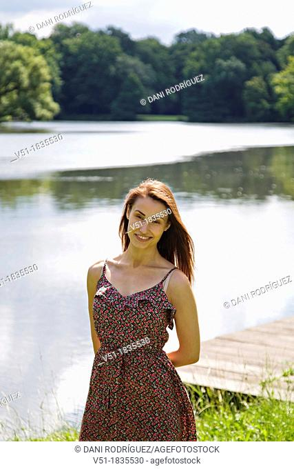 Pretty young woman in lake smiling at camera