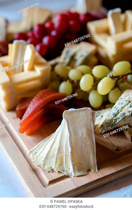 Cheese platter with different cheeses including brie, cheddar and blue cheese, served with grapes