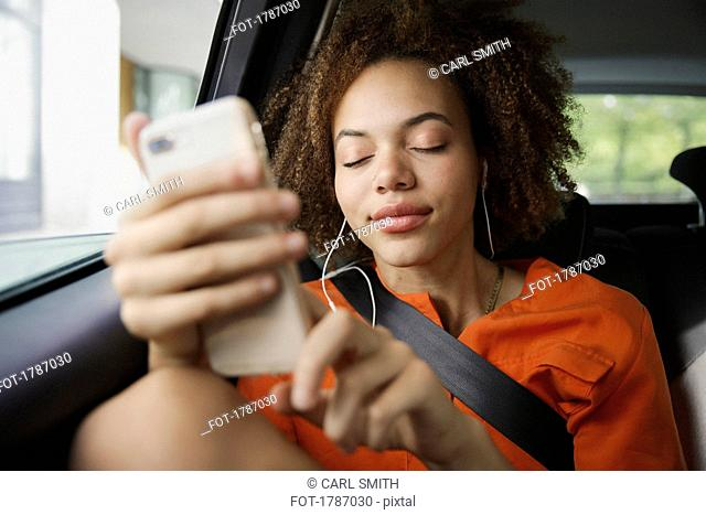 Serene young woman listening to music with headphones and mp3 player in back seat of car