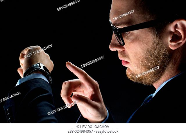 business, people and modern technology concept - close up of businessman with smart watch over black