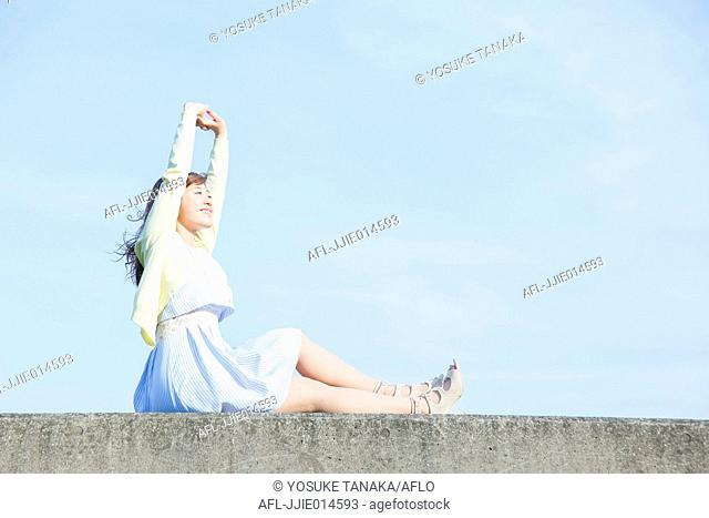 Attractive young Japanese woman stretching outdoors