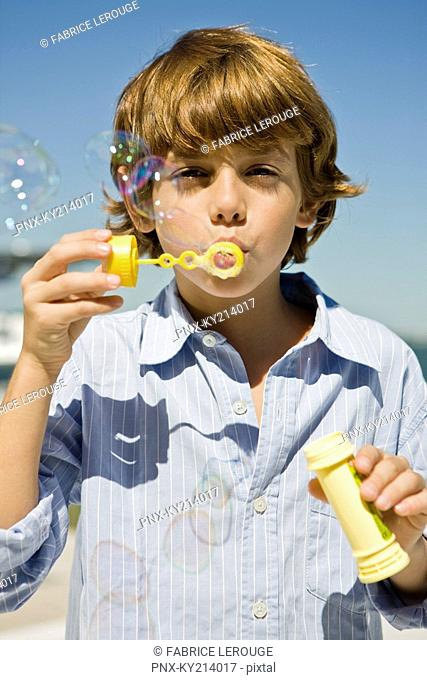 Boy blowing bubbles with a bubble wand